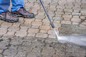 Man cleaning his patio with a pressure washer.