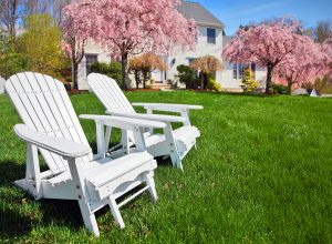 Adirondack chairs in front yard of house with brilliant spring lawn care and landscaping