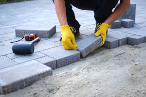 A mason placing concrete pavers to form and outdoor patio