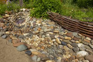 A dry stream made of large stones surrounded by a garden, exhibiting eco-friendly drainage solutions