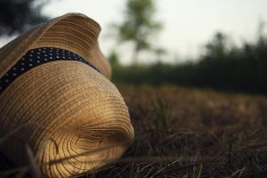 Summer straw hat with blue ribbon and dots lay at dry end summer grass.